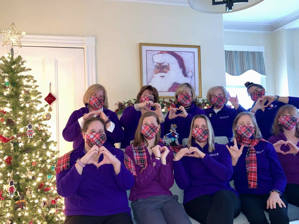 Aberdeen home care office team holding up hearts with their hands and standing next to a beautiful Christmas tree
